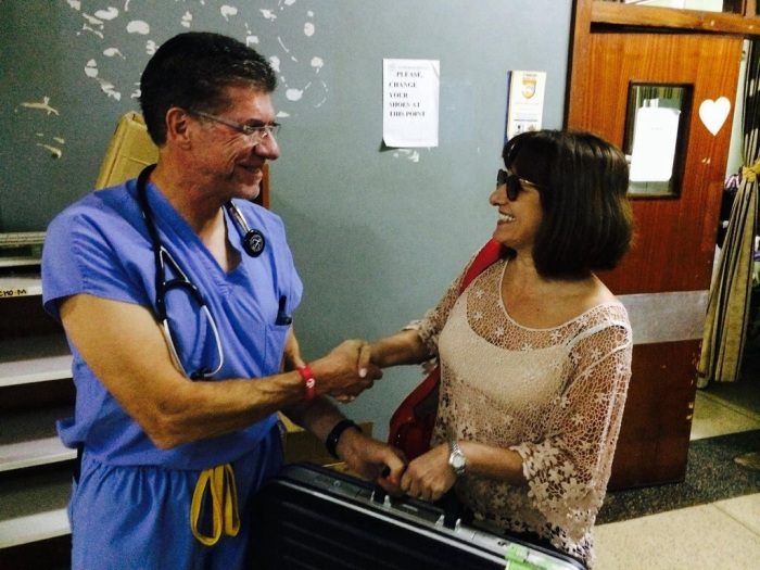 Lucy, Nurse who travels with Chain of Hope Missions handing off the TEE probe to Dr. Cordes